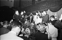 Image of The Beatles standing around a drum kit with reporters at press conference in Maple Leaf Gardens.