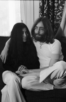 John Lennon, seated cross legged on a chair, with his arm around Yoko Ono [at King Edward Hotel].