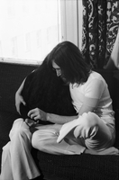 John Lennon, seated cross legged, embracing Yoko Ono [at King Edward Hotel].