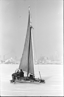 "Ice boat ""Silver Heels"" out on frozen Lake Ontario off the Toronto Islands, city of Toronto in background."
