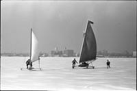 Two ice boats, in an informal ice yachting race, on frozen Lake Ontario off the Toronto Islands, city of Toronto in background.