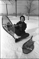 Woman, seated on the snowy ground, lacing up snowshoes.