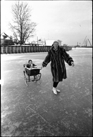 Woman skating, with a child in a pram, on frozen Lake Ontario off the Toronto Islands.