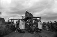 Image of labourers in a field posing with a large piece of farm equipment.