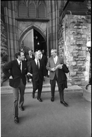 Pierre Trudeau, Justice Minister, Mitchell Sharp, Finance Minister, and Jean Marchand, Minister of Manpower and Immigration, among a group exiting a building in Ottawa.
