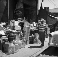 "A man walking past house wares, including breadboxes and large pickling jars, displayed on sidewalk in front of shop with window sign marked ""A. Litvak Groceries & Vegetables."""