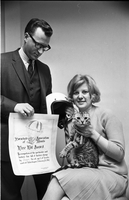 "Man presenting a Parachute Association of Toronto ""Free Fall Award"" certificate and crash helmet to Helen Kupari, and her cat, Jasper."