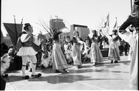 Women in traditional dress, and a man in fustanella costume, dancing in front of crowd gathered in Nathan Phillips Square outside Toronto City Hall