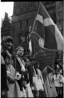 Children, in Greek national costume, standing in line in front of Old City Hall; banner and flag in background with Greek writing