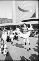 Young men, in fustanella costumes, dancing in front of crowd gathered in Nathan Phillips Square outside Toronto City Hall