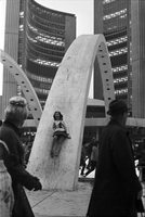 Girl (Carol Russell) slides down one of the concrete arches over the skating rink at Nathan Phillips Square; people ice skating and City Hall building are visible in background.