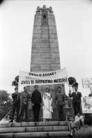 "Anna Tsarnas, dressed as ""Greece in chains,"" with other protesters, under a Greek banner on the 48th Highlanders Regimental Memorial"