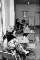 A woman sitting at a table in the beverage room at The Everene Hotel on Jarvis Street, man and two women in background.