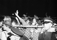 Crowd at airport to welcome The Beatles, two Ontario Provincial Police (OPP) in foreground (one leaning forward out of the frame, the other with fingers in his ears).